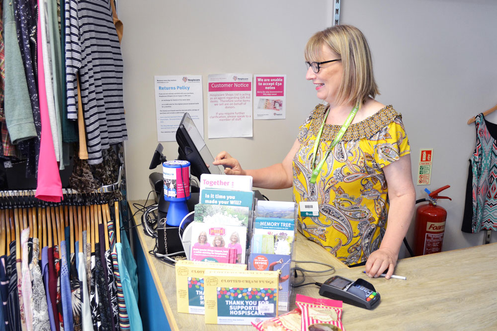 Volunteer Liz at the till in a Hospiscare charity shop