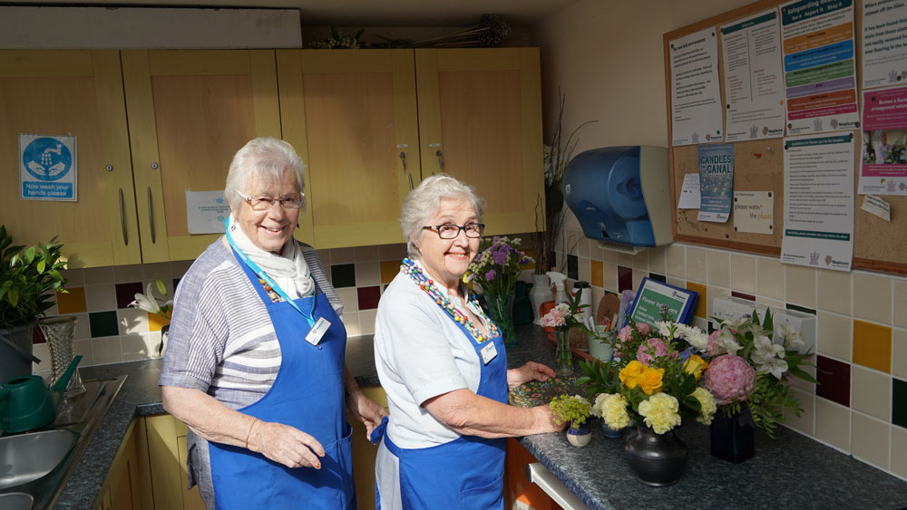 Hospiscare flower volunteers Mo and Ruth looking at the camera