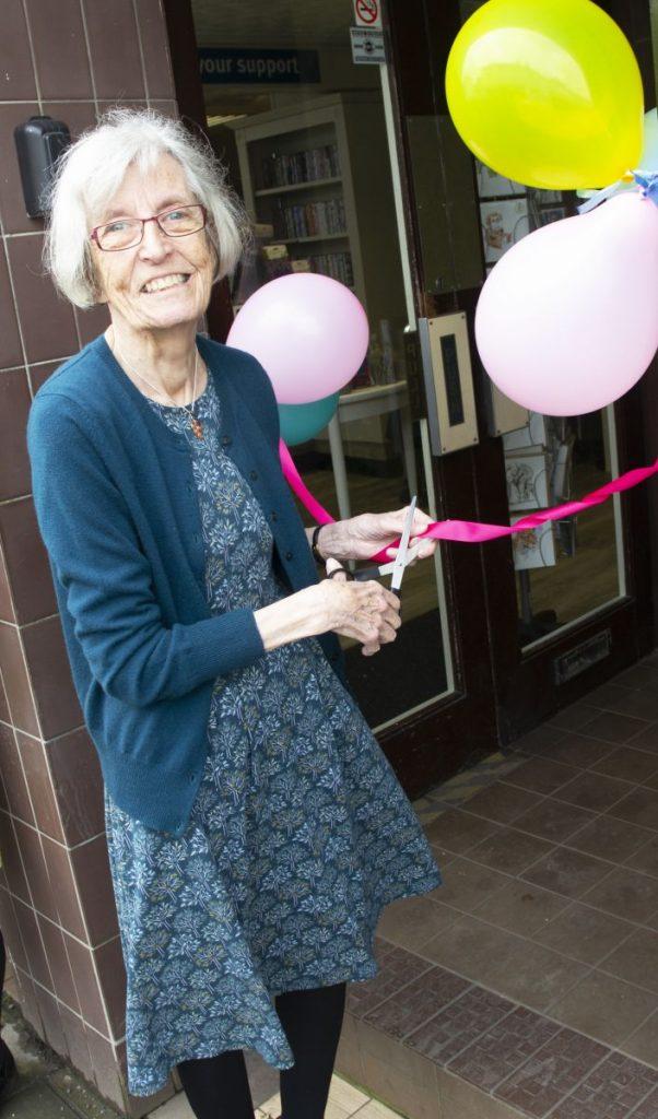 Hospiscare volunteer Margaret cutting a ribbon