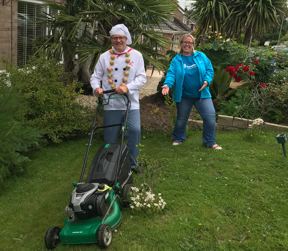 Hospiscare supporter Paul Godfrey dressed as a chef mowing the lawn