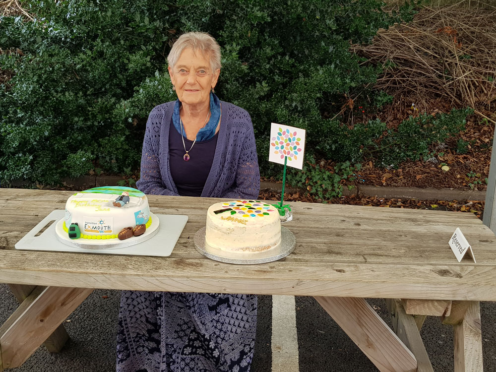 An elderly woman with two birthday cakes