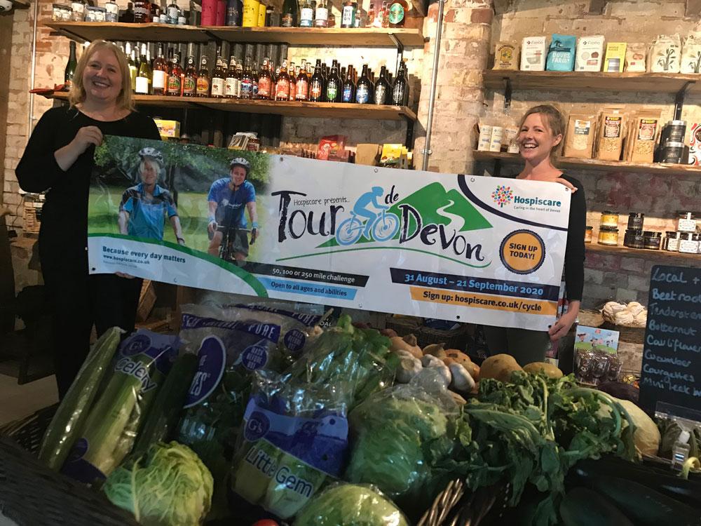 Two women in a farm shop holding a Tour de Devon banner