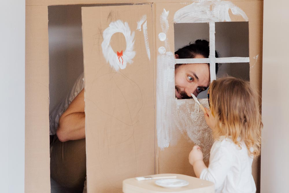 Father and daughter making a cardboard playhouse together