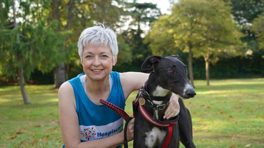A woman wearing a Hospiscare vest and a black and white dog