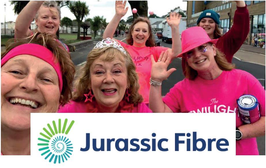 Women waving wearing pink t-shirts with Jurassic Fibre logo overlaid