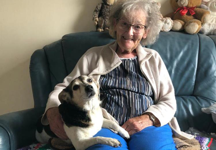 An elderly lady with her dog on her lap