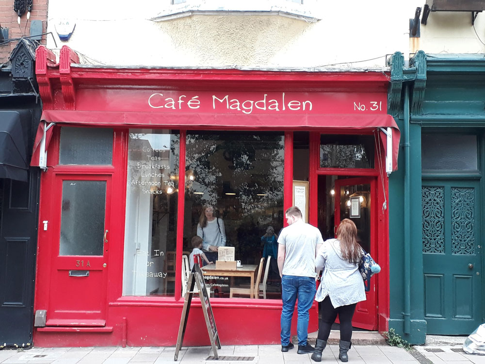 Two people standing outside Cafe Magdalen