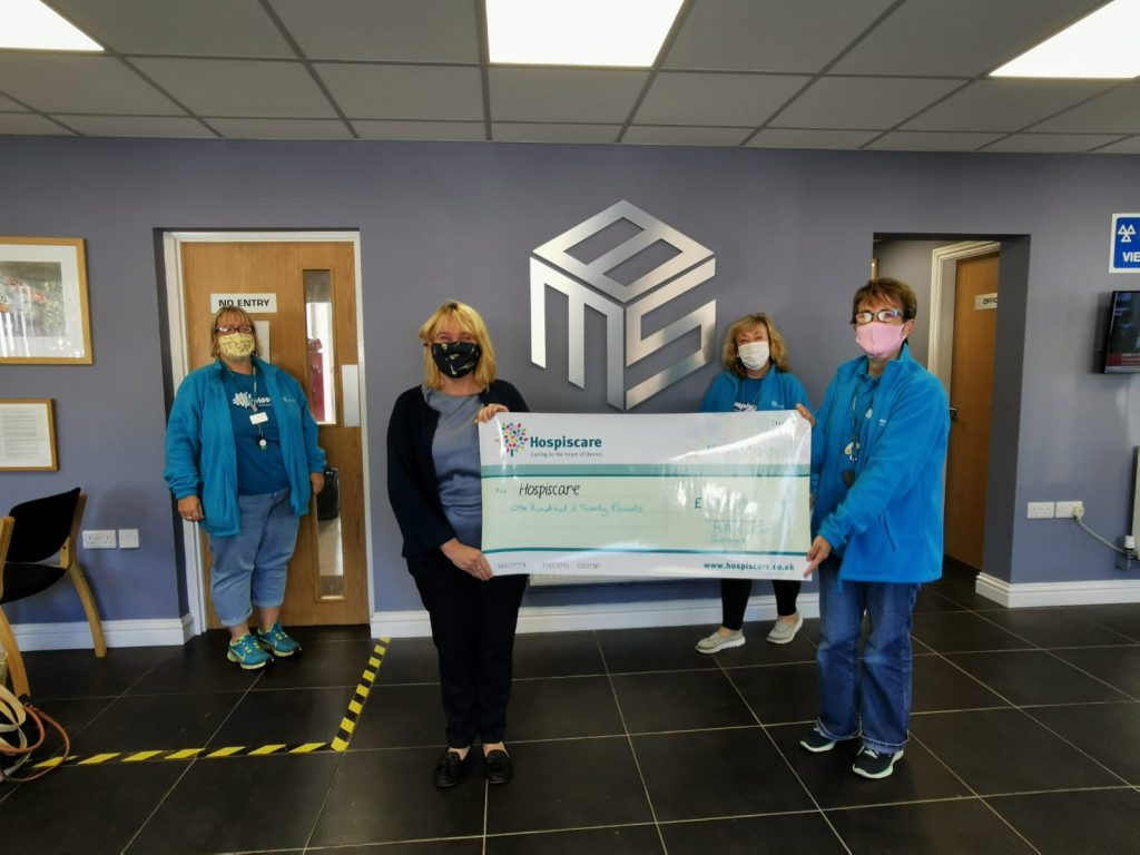 A group of socially distanced people wearing masks and holding a big cheque