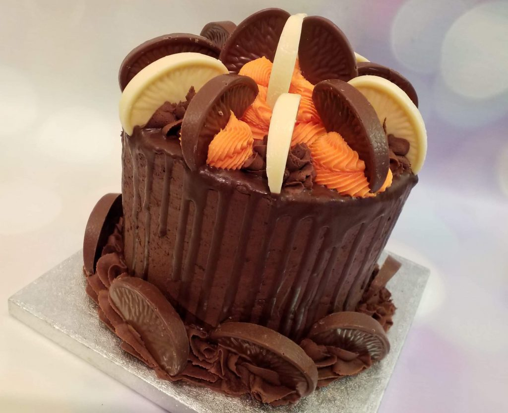 An iced chocolate cake topped with chocolate orange segments