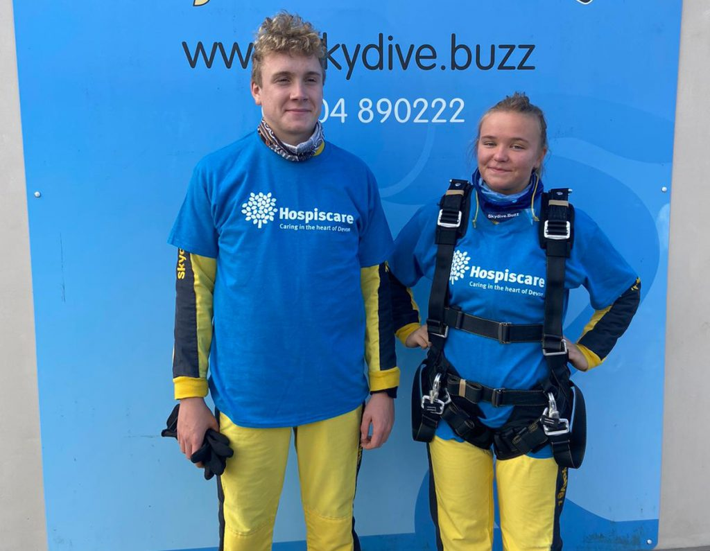 A teenage boy and girl wearing skydive gear