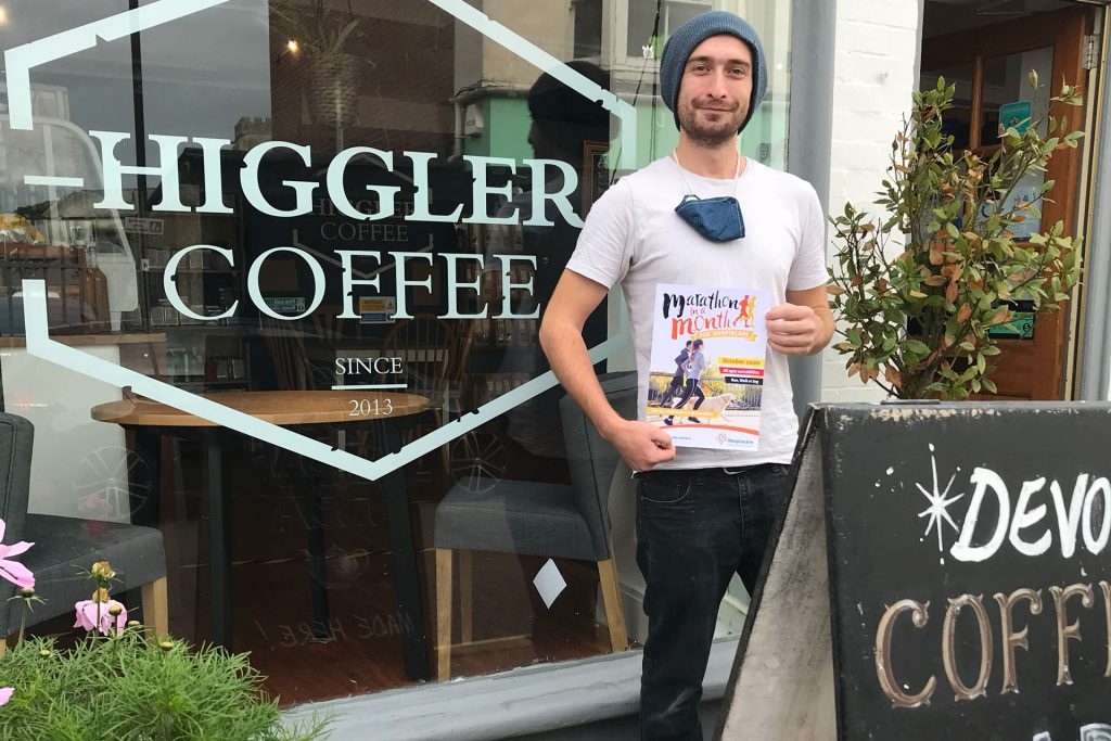 A man holding a cup of coffee outside Higgler Coffee