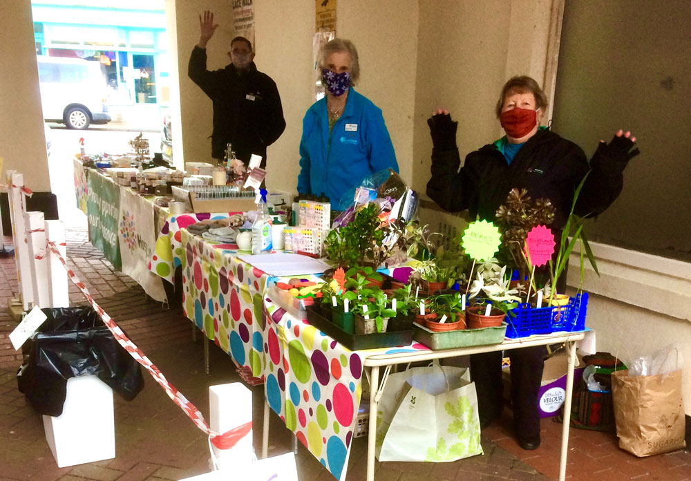 Three people wearing masks behind a table top sale