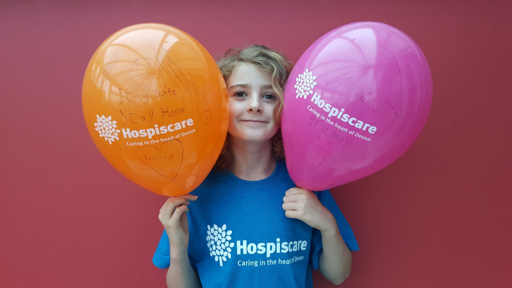 A boy wearing a Hospiscare t-shirt and holding two balloons