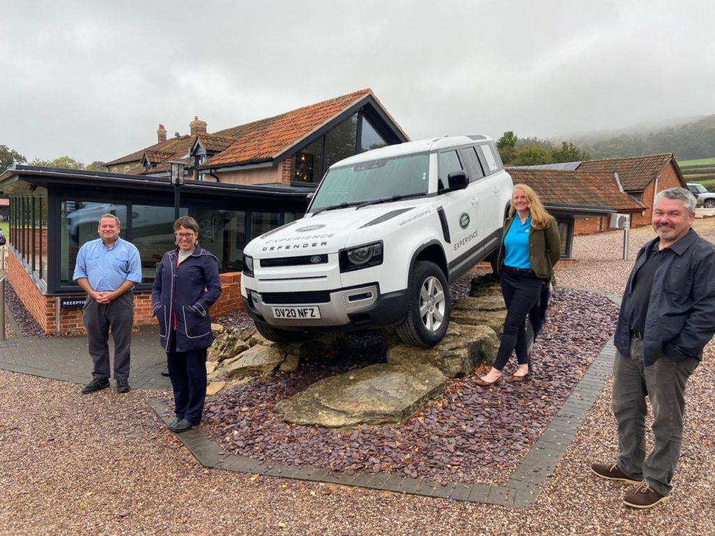 People standing around a white landrover