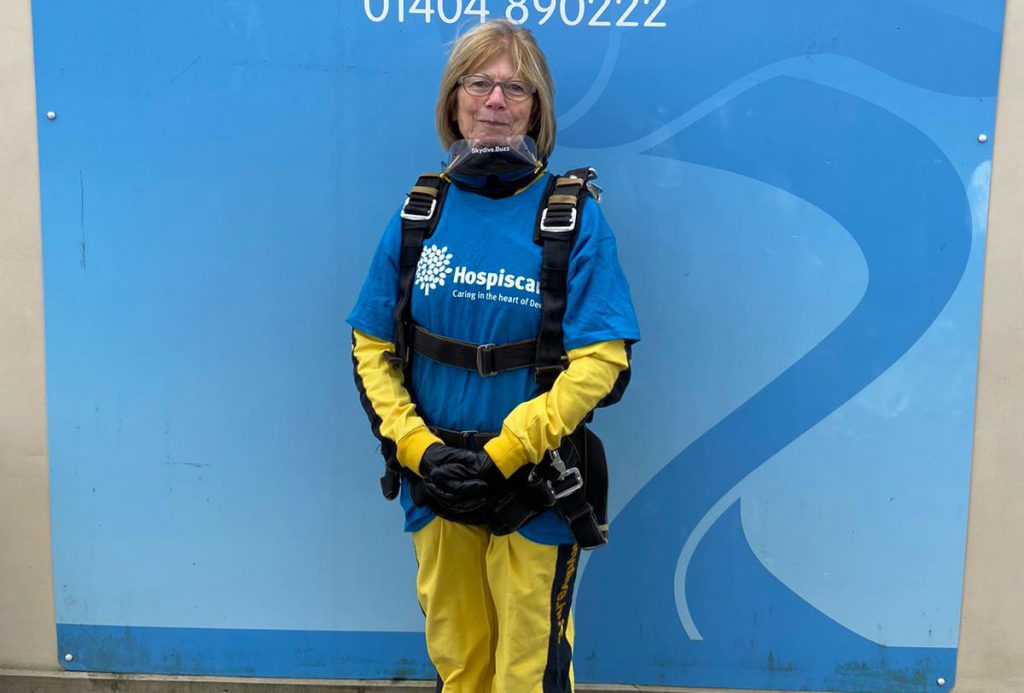 A woman in front of a blue background wearing skydiving gear