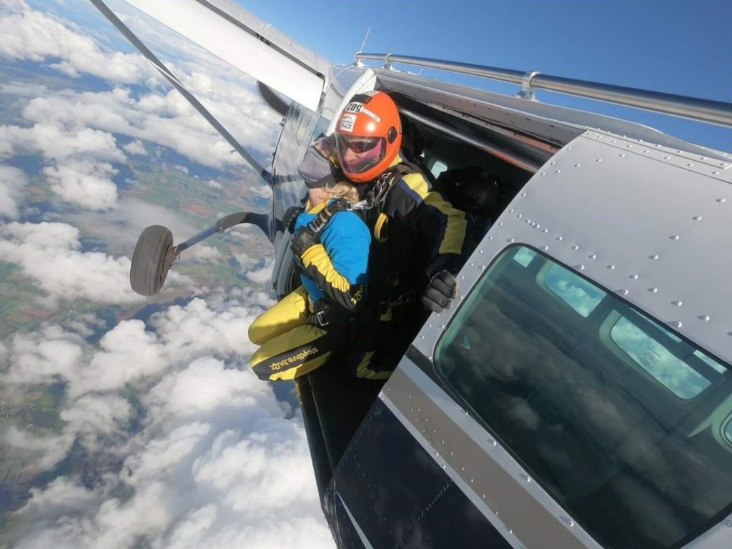 A man and woman jumping out of a plane in a tandem skydive