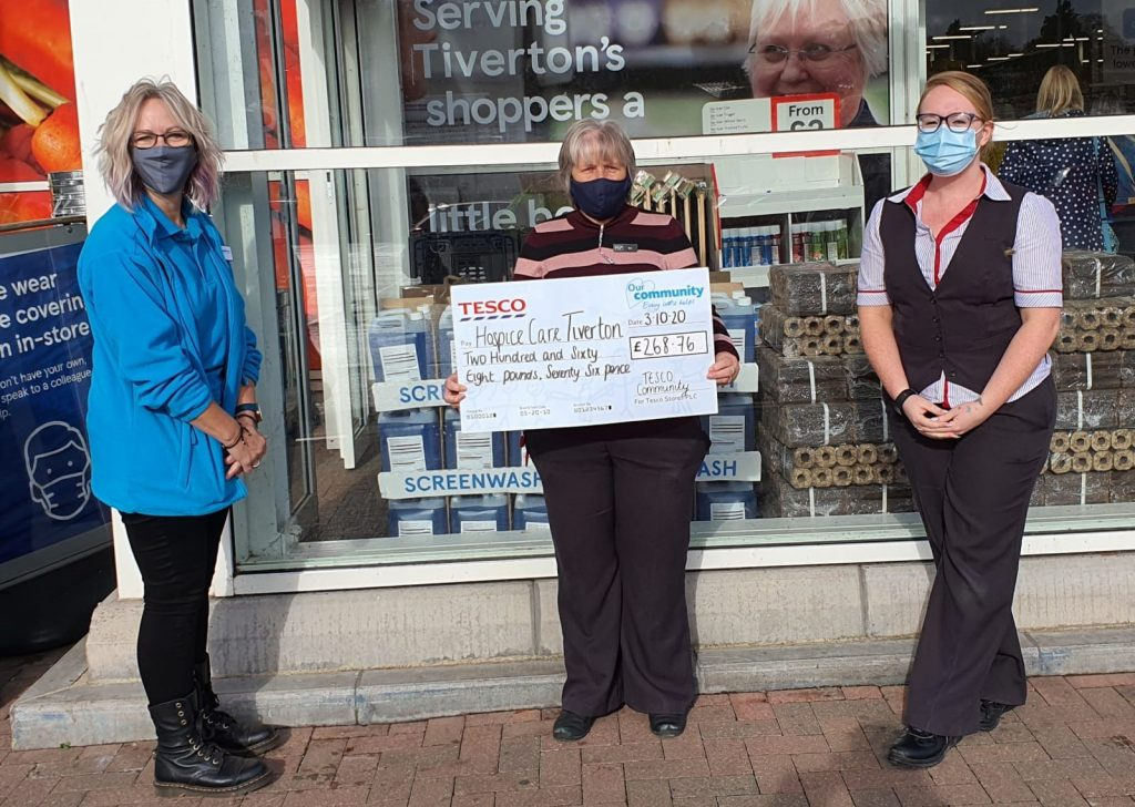 Three people wearing masks holding a big cheque