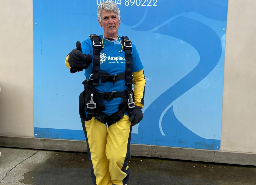A woman wearing skydiving gear pointing at the camera
