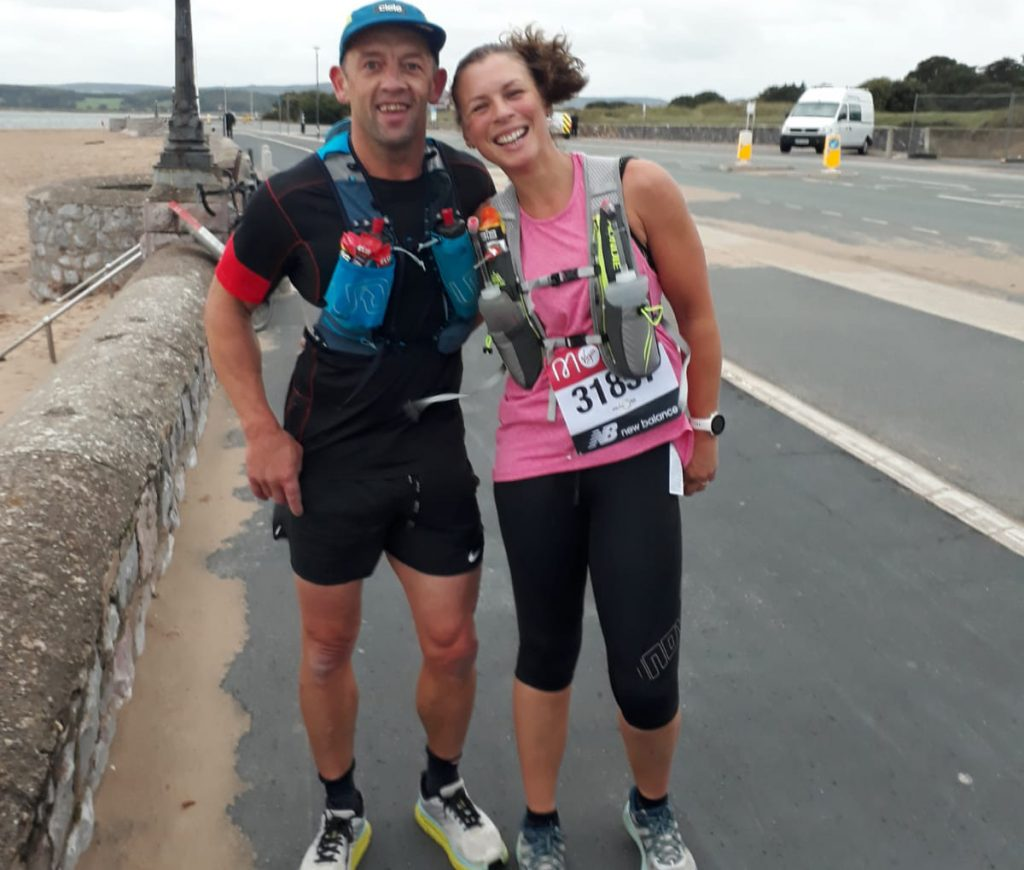 Two runners standing on Exmouth sea front