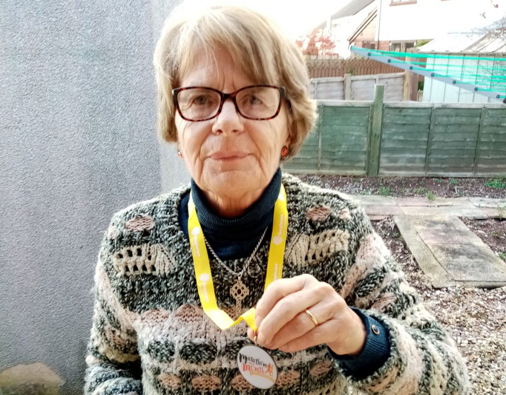 A woman holding up her Marathon in a Month medal