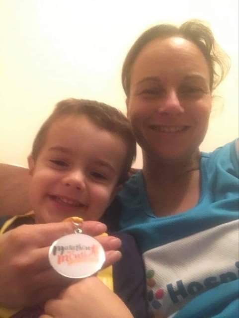 A young boy and his mum with a medal