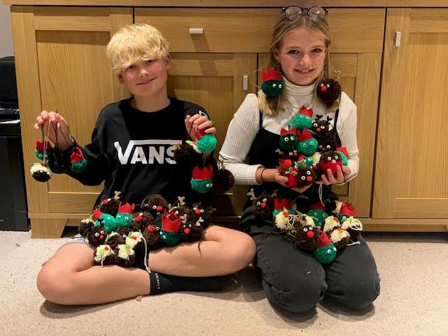 Two children holding Christmas tree pom poms