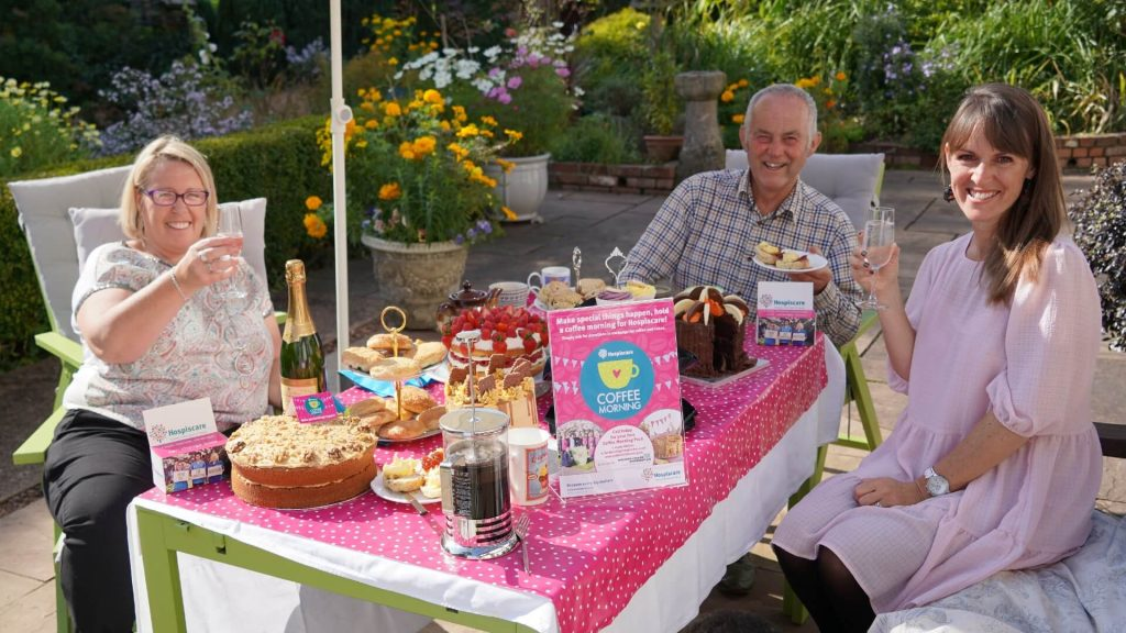 Three people in a sunny garden around a table filled with cakes, coffee and champagne
