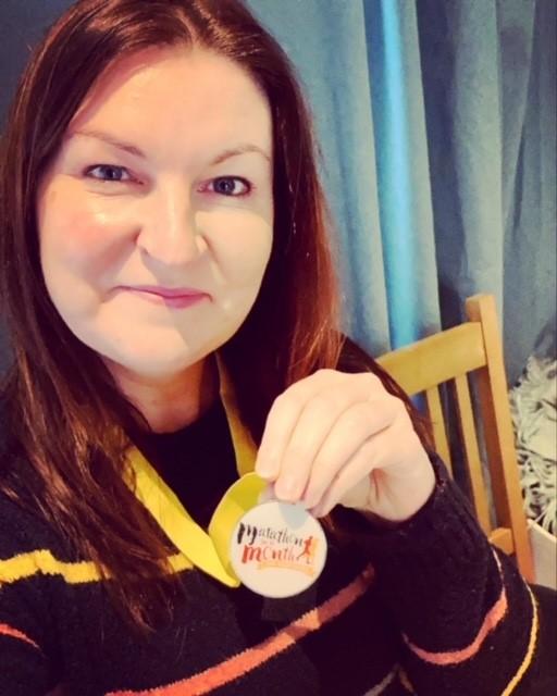 A woman holding a marathon medal