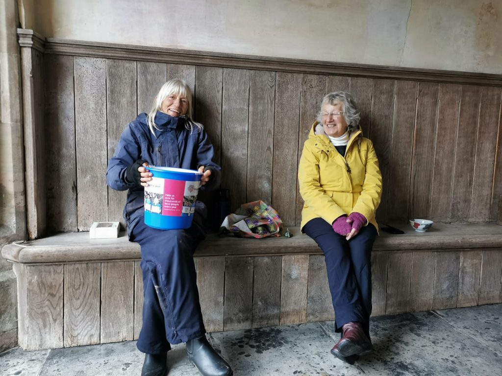 Two women sat on a wooden bench holding a collecting bucket for Hospiscare