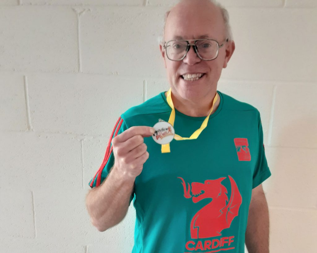 A man wearing a Cardiff shirt holding a medal