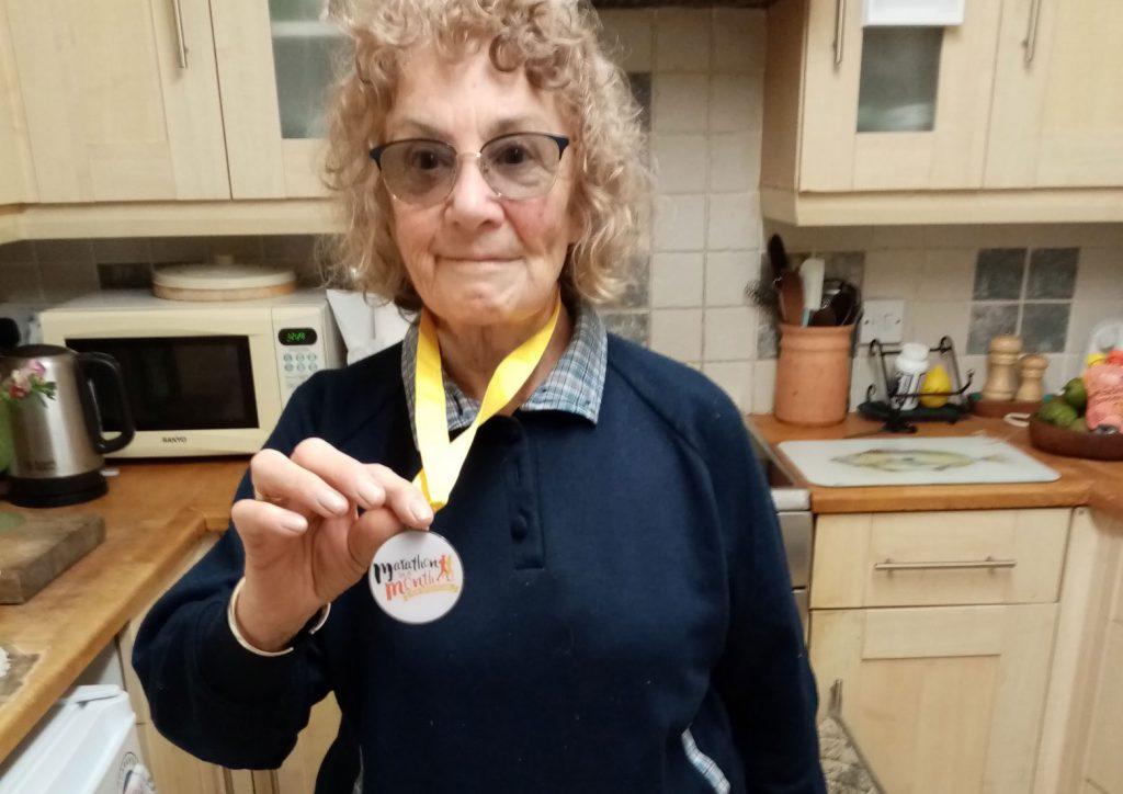 An elderly lady holding a marathon medal