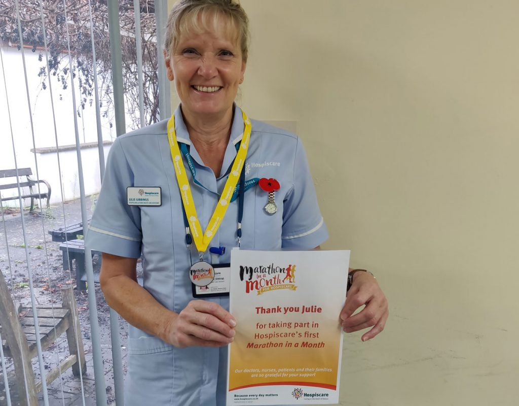 A Hospiscare nurse wearing a medal and holding a certificate