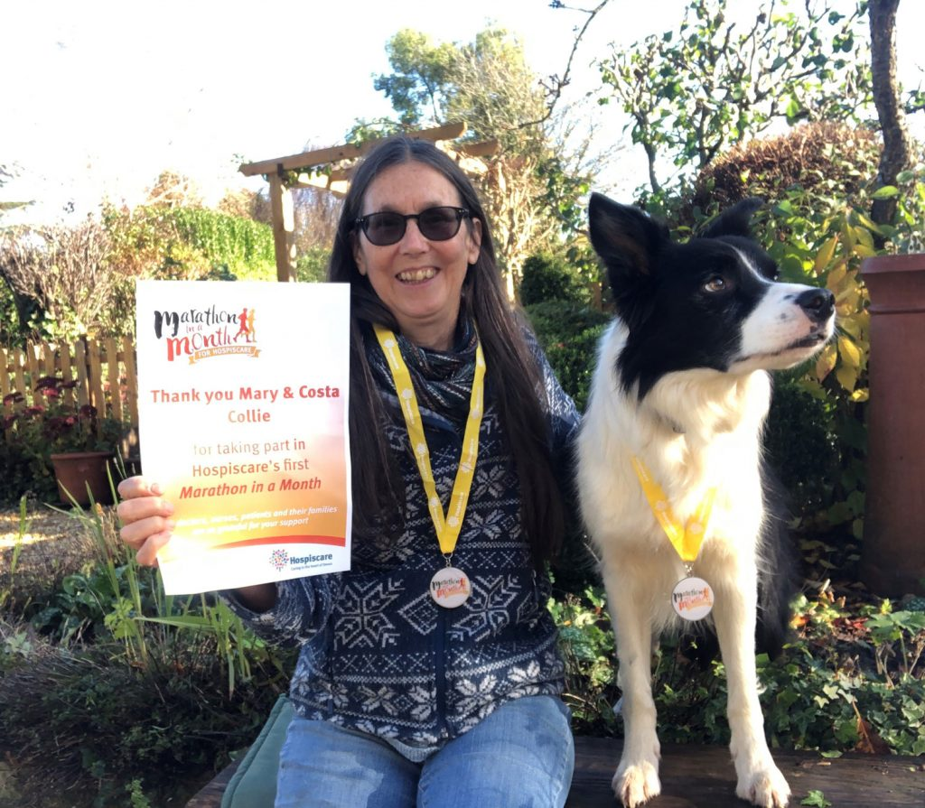 A woman with a medal and certificate next to a collie dog