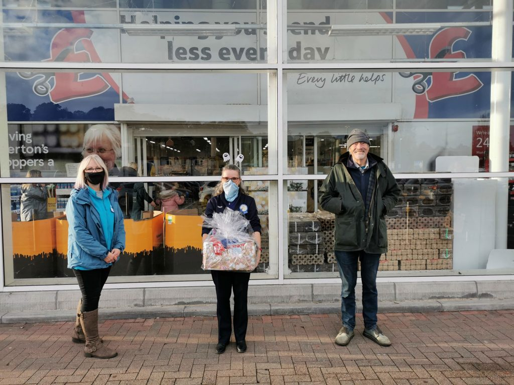 Three people standing socially distanced in front of Tesco