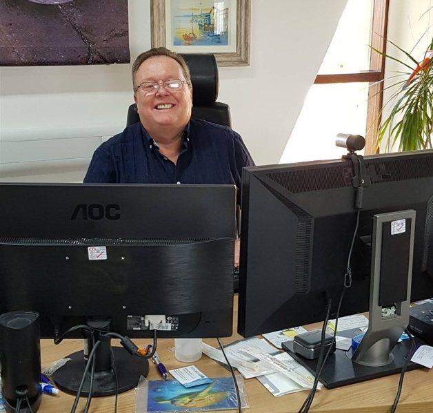 A man at a computer smiling