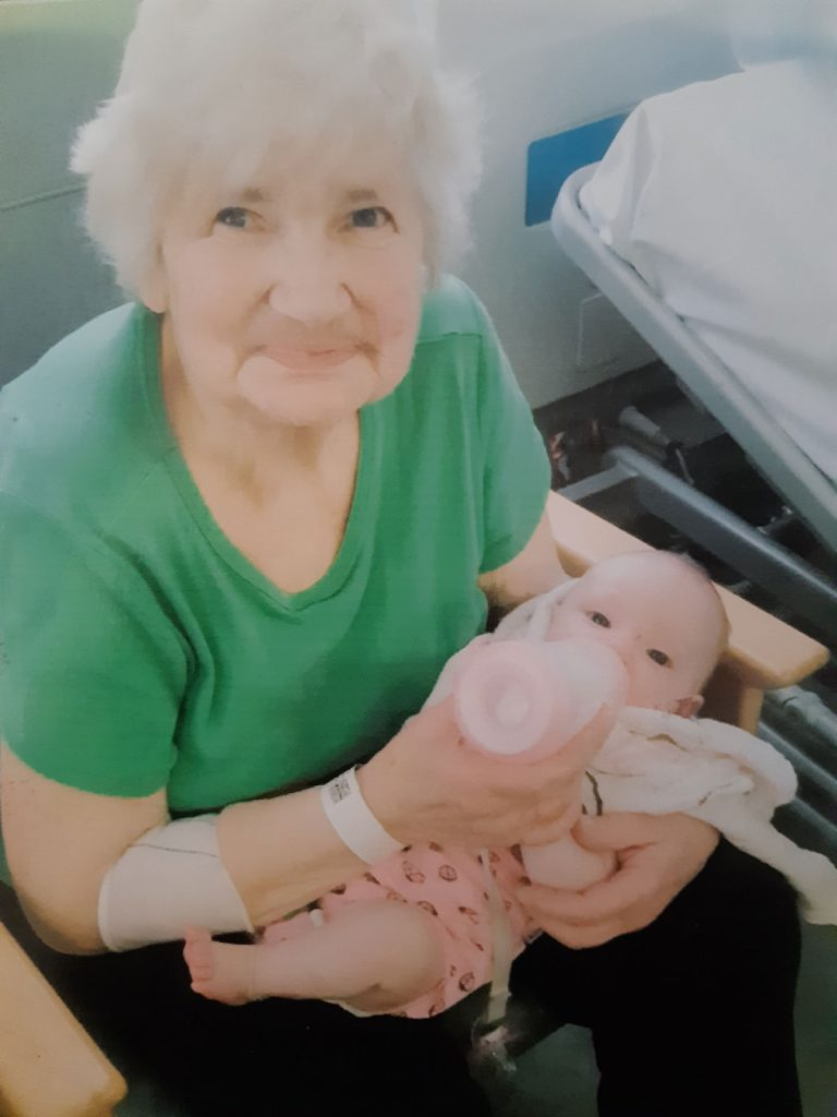 An elderly lady feeding a baby its bottle