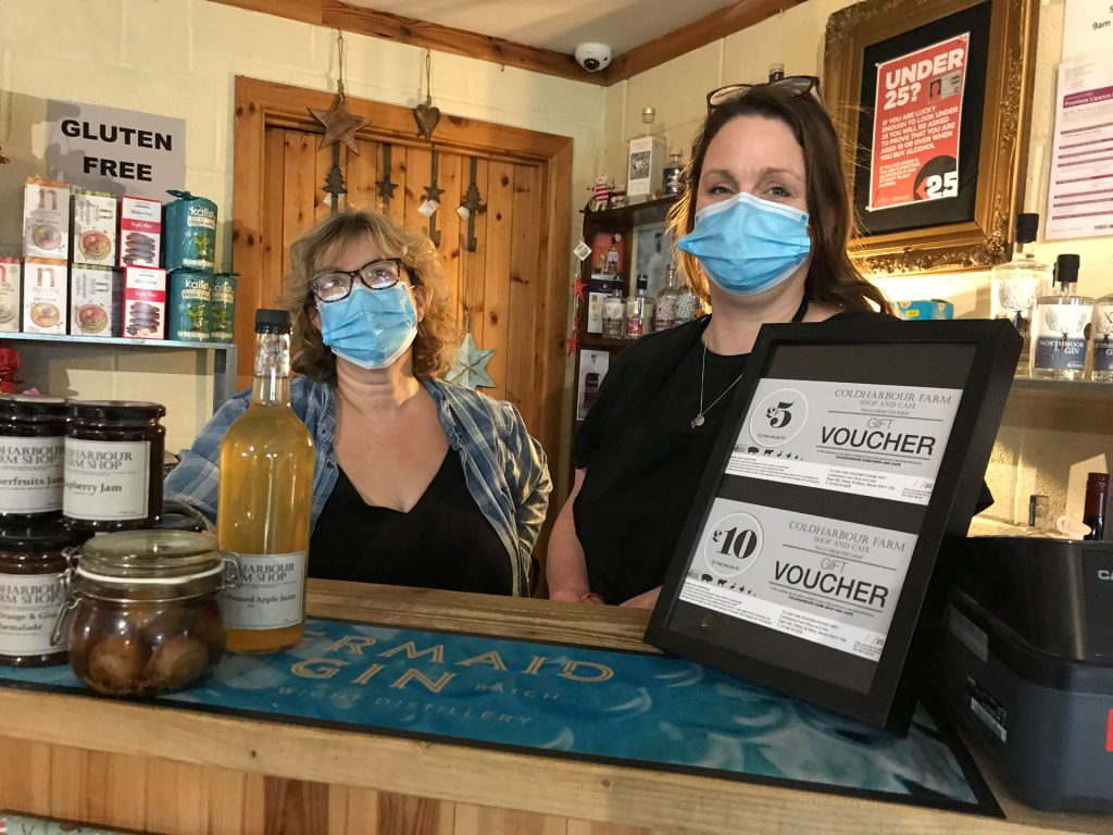 Two women wearing masks behind a farm shop counter