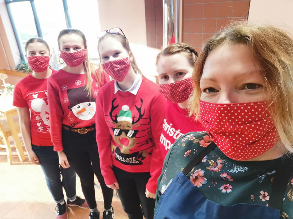 Women wearing Christmas jumpers and red face masks