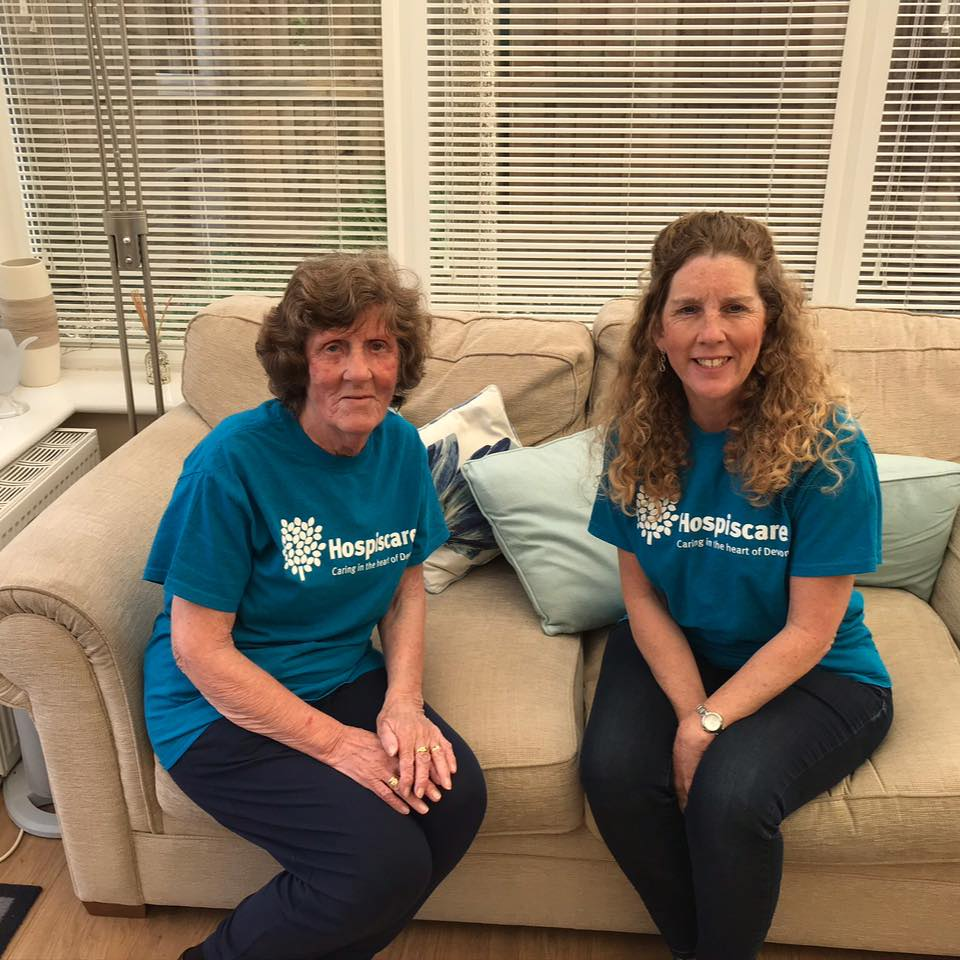 Two women sitting on a couch wearing Hospiscare t-shirts