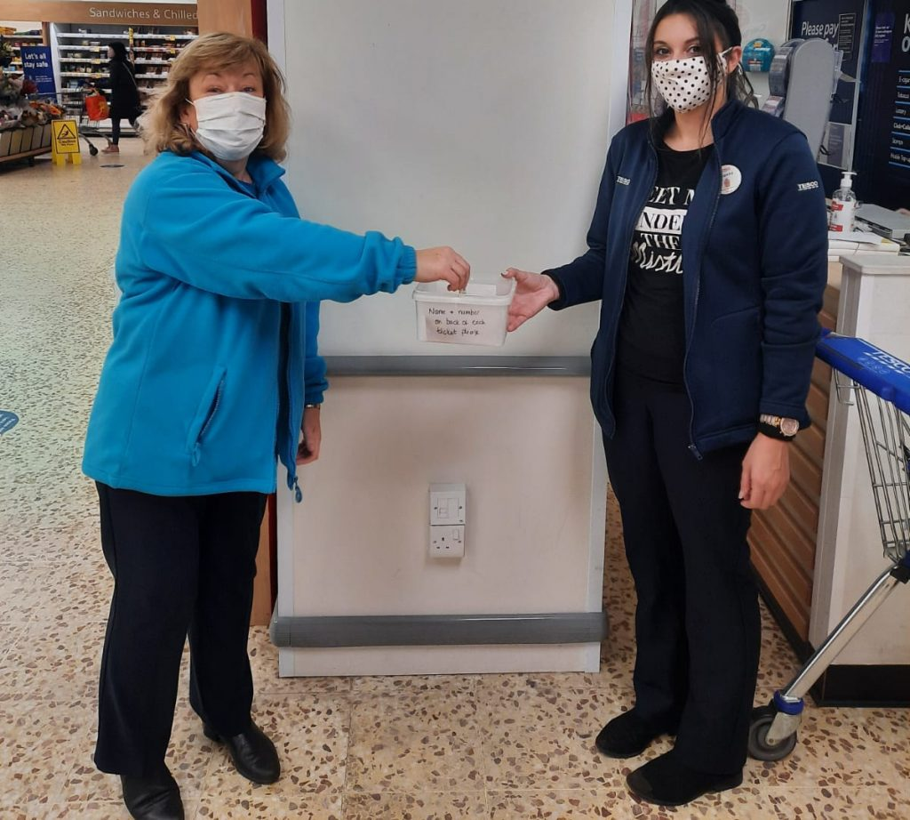 Two women wearing face masks in Tesco with a donation pot