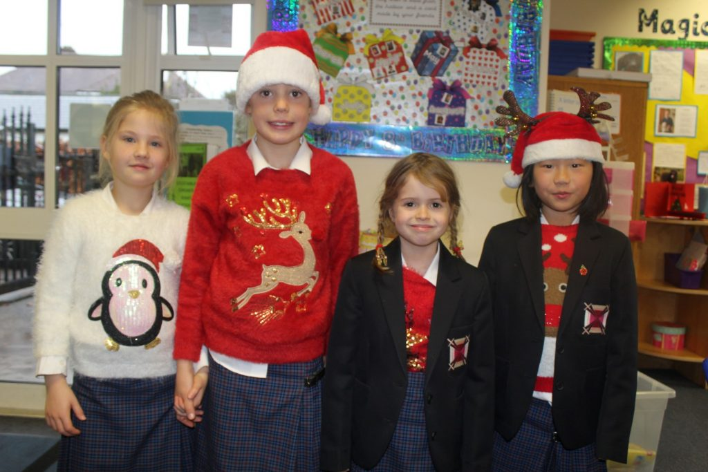 Four school girls wearing Christmas jumpers