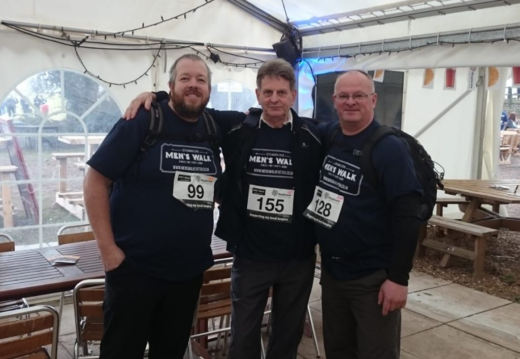 Three men in a marquee wearing Men's Walk t-shirts