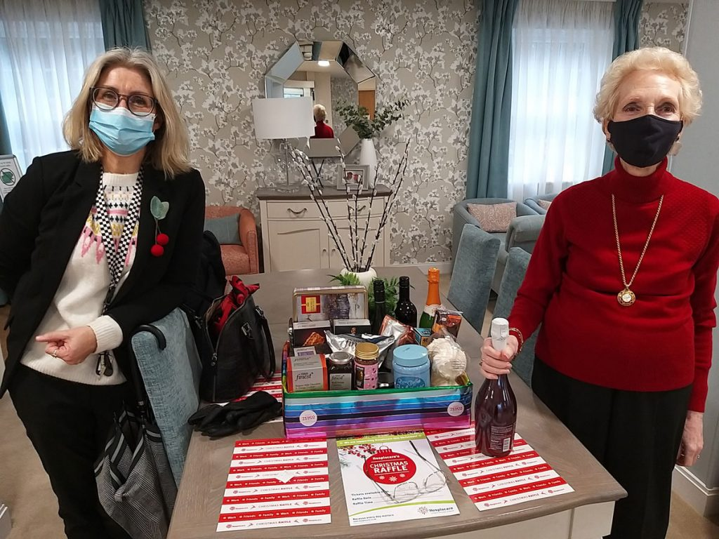 Two women wearing face masks standing either side of a hamper