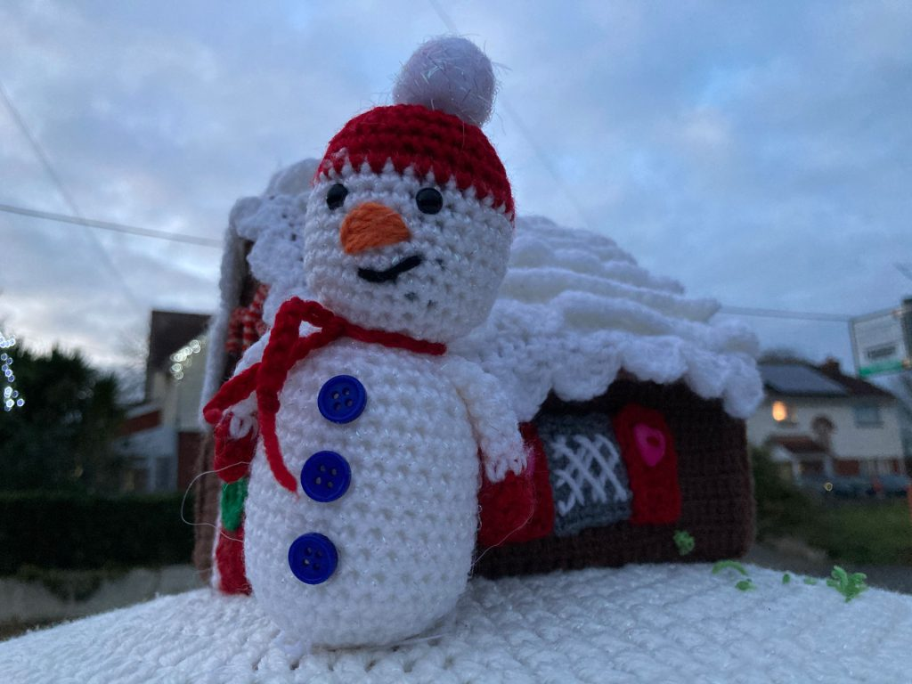 A knitted snowman scene on top of a postbox