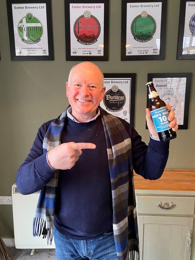 A man holding an Exeter Brewery Men's Walk beer bottle