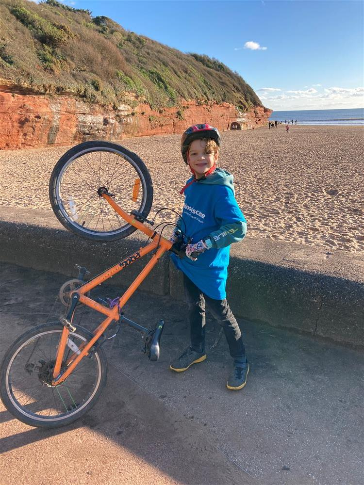 A young boy holding a push bike on Exmouth seafront