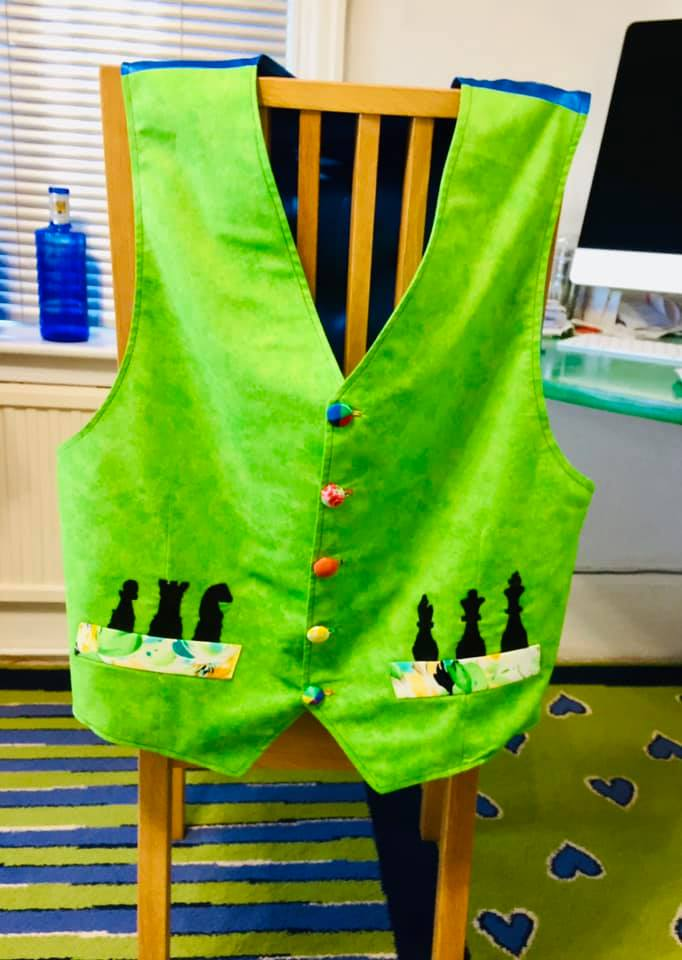 A green waistcoat with chess pieces as details
