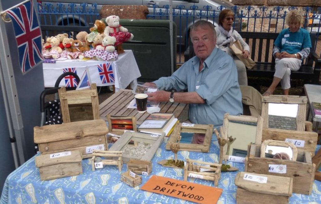 A man sitting at a table top stall sending wooden crafts
