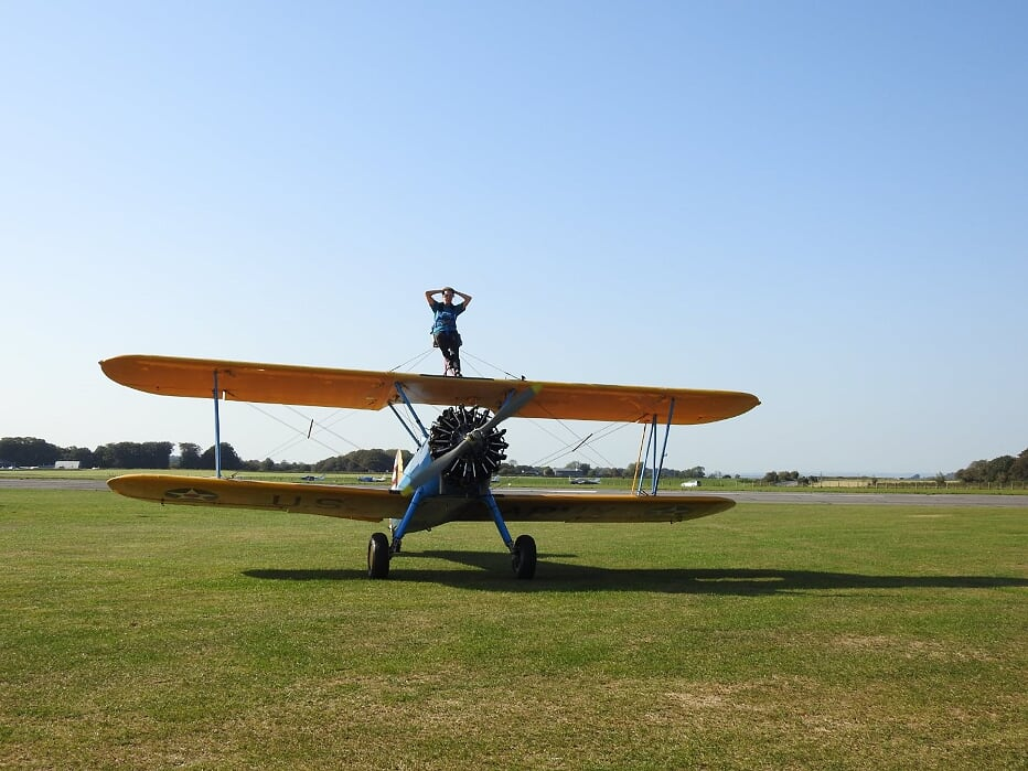 A woman strapped to a bi-plane before take-off