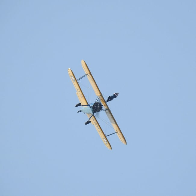 A person on top of a bi-plane mid flight